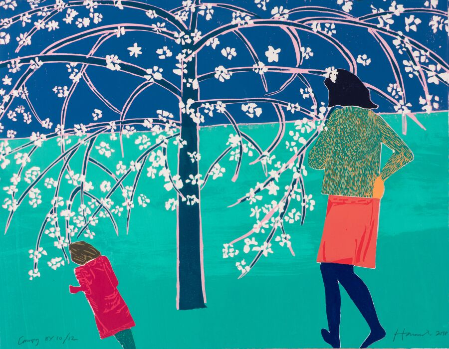 Woman and child standing under blossom tree.